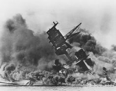 Picture of dramatic sinking of USS ARIZONA, with the loss of 1,177 lives, during the Japanese attack on Pearl Harbor on 7 December 1941, the event that brought about U.S. involvement in World War II. The picture is taken looking from the side of the USS Arizona. To the left you can Number Two 14″/45 triple gun turret pointing forward. The supporting structure for the gun director tripod has collapsed and the tripod is tilting forward towards the front of the ship giving the wreck its…