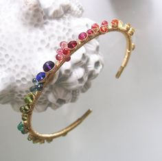 .........classic beauty.......  Thick 12 gauge 14k solid gold wire has been forged into a cuff style bracelet. Adorned with tsavorite, emerald, vesuvianite, tourmaline, peridot, blue sapphire, tanzanite, amethyst, fiery orange and red sapphires, red spinel, pink sapphire, and yellow sapphires. Wrapped in thinner gauge 14k solid gold wire.  Bracelet measures 5 7/8 from end to end. Gap is 1. Total circumference is 6 7/8.  Thank you, Tracey  Bellajewels 14k gold cuffs:: http://etsy.me/2f5FZ8F…