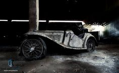 This vintage racing car and classic abandoned Jaguar were photographed by an urban explorer in a neglected building in Portugal.