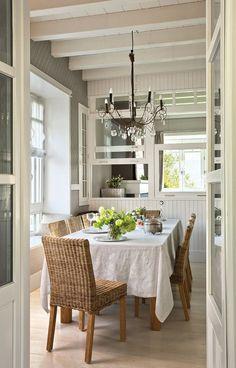Comedor con sillas de mimbre y hueco pasaplatos a la cocina. Tres ventanas de guillotina