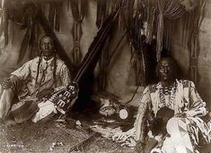 You are looking at an intriguing picture of Two Indians in a Piegan Tipi. It was taken in 1910 by Edward S. Curtis.    The picture presents Little Plume and son Yellow Kidney seated on ground inside lodge, pipe between them.    We have created this collection of pictures primarily to serve as an easy to access educational tool. Contact curator@old-picture.com.