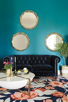 Blue wall, navy couch, gold mirrors, white and gold coffee table