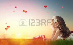 mujeres naturaleza: Niño de la muchacha dulce mirando globos rojos. Globos en forma de corazón volando en el cielo del atardecer. Boda, San Valentín, el concepto de amor.