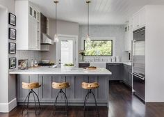 White and gray kitchen features gray distressed cabinets paired with white marble countertops and a white and gray marble herringbone tile backsplash. A farmhouse sink and deck mount faucet stands under a picture window next to a corner glass door which leads to the backyard. A shiplap ceiling is accented with two glass pendants which hang over a gray kitchen peninsula lined with Arteriors Henson Counter Stools.