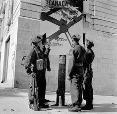 """Canadian soldiers looking at the """"Canada Town"""" billboard, Campobasso, Italy, 21 October 1943. (item 1)  (L-R): Private Nelson Boyce, 48th Highlanders of Canada; Lance-Corporal Claude Bell-Smith, Royal Canadian Regiment; Private George MacDonell, 48th Highlanders of Canada; Corporal R.T. Carswell"""