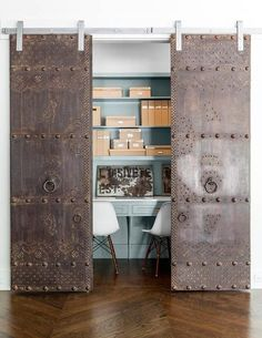 A pair of metal doors on rails open to a closet office filled with a turquoise built-in desks ...