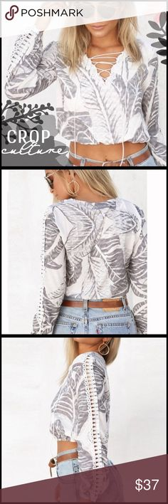 Lace-Up Crop Top Lace-Up Crop Top; poly blend; lace-up detailing in front; hollow out crochet lace along arm; Boutique Tops