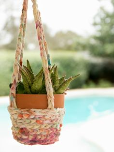 Turn an old T-shirt into yarn that is then used to make a boho inspired hanging basket for plants perfect for turning the patio into paradise.