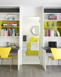 Shared boys' bedroom features separate gray built in desks paired with yellow chairs, West Elm Scoop Back Chairs, flanking a doorway into the bathroom.
