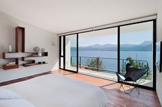 A minimalist décor suits well a bedroom with views of the water and the mountains in the distance