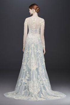 Incorporating color into your wedding day look is an of-the-moment bridal trends. This Oleg Cassini gown features a long-sleeve, lace-appliqued tulle sheath that sits beautifuly over a strapless blue