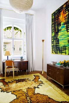 A lion kilim rug, abstract painting and lantern add a pop of flair in this Berlin home.