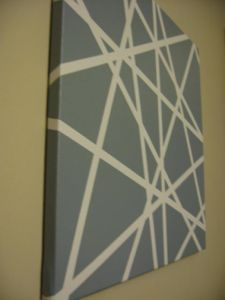 All you need is a canvas, masking tape and spray paint! I like this free form stenciled look for below chair rail!