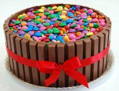 Chocolates Kit Kat e confeitos coloridos cobrem o bolo de aniversário de chocolate com recheio de brigadeiro. Da Nika Linden