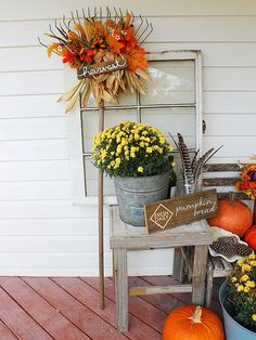 Rake wreaths are beautiful, but it's hard to beat an entire embellished garden rake propped upright on your porch. Corncobs and faux flowers are bundled around rake tines to create this country-inspired decoration, and a hand-painted harvest sign finishes the look. Add outdoorsy details to the vignette, such as jarred pheasant feathers and a charming pumpkin bread signboard, for layers of rustic interest./
