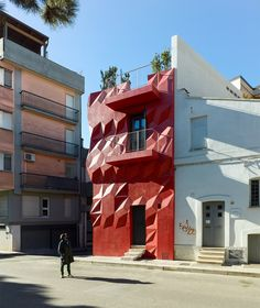 A faceted red surface creates geometric patterns across the exterior of this house in southern Italy