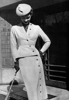 1952 beige wool suit that cuts a sinuous line with the buttons, the neckline reveals a red silk blouse, by Christian Dior