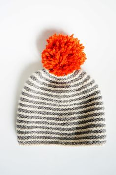 e3b80ad7ff5 a neon orange pompom on a grey - white striped hat - beautiful eyecatcher