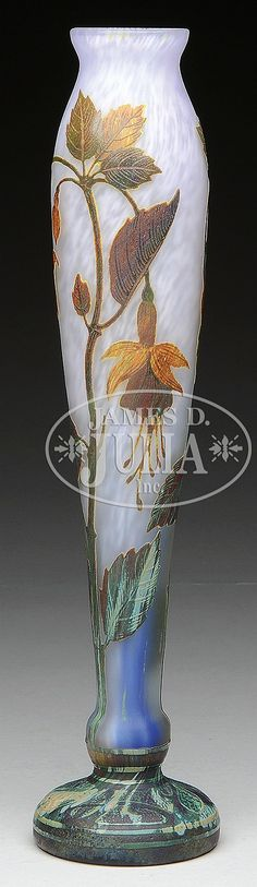 """Daum vase is decorated with vitrified glass cameo fuchsia flowers, stems and leaves. The autumn colored cameo decoration is set against a mottled blue shading to white frosted background. Signed on the side in cameo """"Daum Nancy"""" with the Cross of Lorraine. SIZE: 13-3/4"""" t. CONDITION: Very good to excellent. 16398-153"""