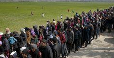 Decenas de refugiados esperan para recibir comida en las inmediaciones de Idomeni. REUTERS/Marko Djurica