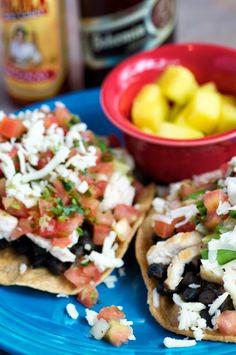 chicken yucatan tostadas; two corn tortillas topped with black bean chorizo mixture, avocado slices, jack cheese, salsa fresca & sliced chicken breast.