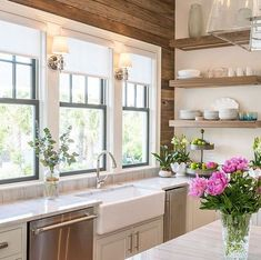 white kitchen with farmhouse sink and wood accent wall More