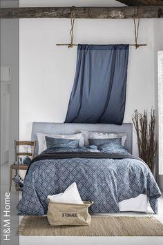 Das Schlafzimmer erhält seinen maritimen Look vor allem durch die blau gemusterte Bettwäsche in Kombination mit den natürlichen Möbeln. Ein besonderer Hingucker sind die Vorhänge, die mithilfe von Seilen an den Dachbalken befestigt wurden und eine gemütliche Atmosphäre im Raum schaffen. Ein praktischer Leinensack kann für Wäsche oder Kissen genutzt werden.