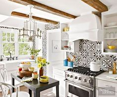Tile patterns in high-contrast color pairings work well in white kitchens. These homeowners maximized the impact of graphic Cuban-style cement tiles by using them to create backsplashes on the range wall and wallpaperlike coverings on other walls. The pumped-up pattern handily highlights the white cabinets, weighty woodwork, and detailed trim./