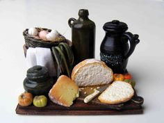 Still life with bread on a wooden board. All the pieces are glued onto the board. Size of the board is 48 x 37 mm.  This miniature is in one inch scale.  This item is for collectors and not recommended under age of 12.