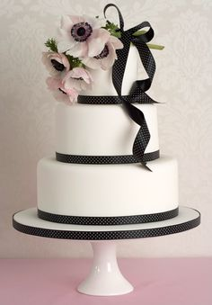 This design is incredibly chic and exquisitely unfussy. A bouquet of fresh blush pink Anemones drapes effortlessly over the simple iced cake trimmed with a black & white spotted ribbon, defining pure elegance.