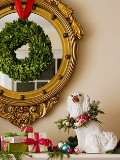 Whimsical Christmas Mantel  - love the humor of this display.  On a living room mantel, a wreath collar embellished with ornaments and tiny rosebuds dresses a Staffordshire dog in holiday finery. Additional ornaments and greenery on the mantel and an everlasting boxwood wreath hung over a mirror reflect an easy-does-it Christmas style.