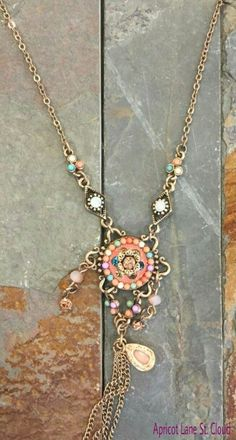 #J2288.  A boho chic necklace that has a slightly antiqued gold chain. The necklace has two stations before reaching the main pendant. The main pendant is done in beautiful colors of peach, coral, mint, and yellow. From the main pendant there is antiqued gold chain fringe and a tear drop charm. To add this necklace to your jewelry box, give us girls of Apricot Lane St. Cloud a call at 320-774-1533 or visit and follow us on Facebook at www.facebook.com/ApricotLaneStCloud and on Instagram…