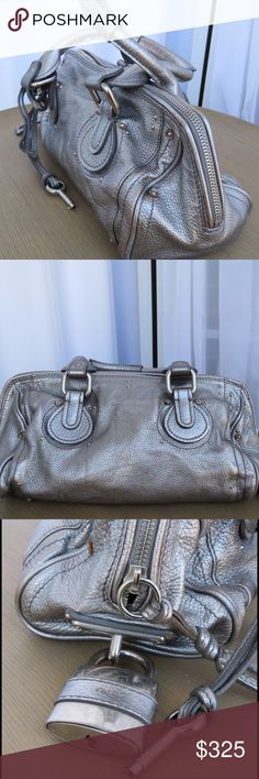 Chloe Metallic Paddington Bag When it comes to lovely, luscious handbags, it's hard to beat the leather masterpieces by Chloe. This eye-catchingly metallic leather is a maze of silver buckles and padlock detail make this doctor-style bag irresistible. This bag features  a top zip with a side padlock and key that can either be used for style or function to  keep your purse contents truly secure. The interior is slightly worn with a few minor stains, but overall is a gently used purse still in…