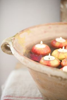 Floating apple candles in a rustic clay bowl.Ideal for a outdoor table setting.