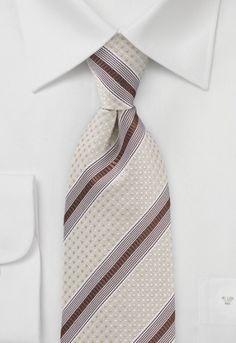 Sul fondo a puntini bianco di questa cravatta dal delicato color beige sono presenti delle righe bianche e marroni. La cravatta tessuta in seta è stata lavorata a mano.