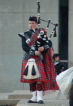 A bagpiper and member of the Queen's Bands wearing a full plaid in traditional highland dress.