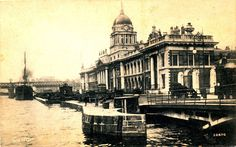 Vintage postcard of the Custom House in Dublin, Ireland. Shows the wharf, bridges, people and horse and carts.