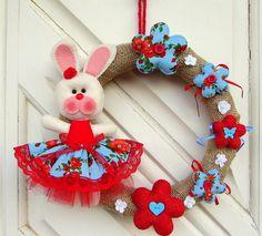 Guirlanda com coelha de páscoa, confeccionadas em feltro. Flores em tecido e feltro. <br>Pode ser feita em qualquer cor. <br>Diâmetro da guirlanda: 26 cm