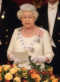 "The Queen making a speech at the State banquet for the President of South Africa at Buckingham Palace on 3rd March 2010. She is wearing the Queen Mother`s Lily (or ""Foot Long"") brooch. A present from her husband George VI. To go with the brooch the Queen wore Queen Alexandra`s Kokoshnik style diamond tiara, the necklace & bracelet given to her by the people of South Africa for her 21st birthday in Cape Town in 1947 & Family Orders etc.."