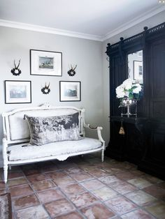 love the juxtaposition of the cool gray walls, the luxurious velvet pillow, the dark wood with the warm white-washed tile floor. It's yummy!