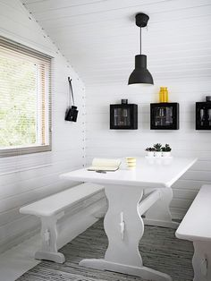 Bright white helps this small summer house dining area feel more spacious.