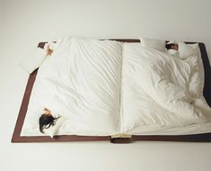 book bed looks like a book with pages as covers and pillows as bookmarks. created by Japanese artist Yusuke Suzuki
