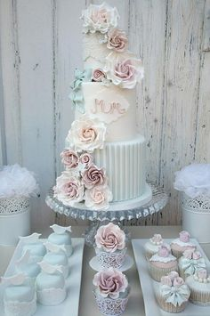 Stripes, fondant roses and a simple monogram combine on this three-tiered wedding cake in vintage hues.