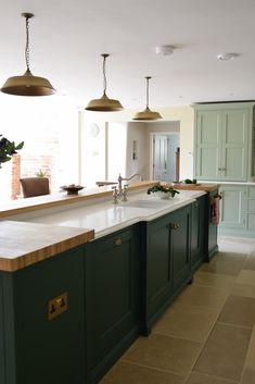 This rather majestic island was the concept of our client, lovingly built, according to their wishes.  The island houses 2 Siemens dishwashers and 2 Caple wine cabinets, with plenty of additional storage in a mix of glazed and solid door cabinets.  The Armac Martin Cotswold hardware in burnished brass beautifully compliments the green island, painted in Hunter Dunn by P&P Library. Main cabinetry is LG Boringdon Green, the walls in F&B Old White. The Caesarstone worktop is in crisp Frosty Carina. Solid Doors, Wine Cabinets, Kitchen Islands, House 2, Kitchen Inspiration, Food Preparation, Foyer, New Homes