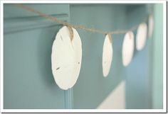 Easy to make...take sand dollars & loop twine through the holes at intervels...hang where ever you please ;)