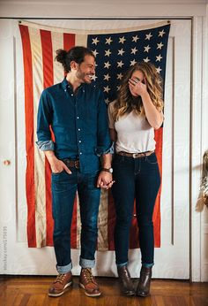 Hipster couple standing in front of American Flag by Trinette Reed