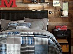 lit et table de chevet en bois noir, literie en gris et bleu et étagères murales tuyaux
