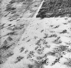 battle Of The Bulge - Aerial view over Ardennes showing shell bursts in the snowy plantation in a clearing of the forest near Langlir during the Battle of the Bulge. 1945