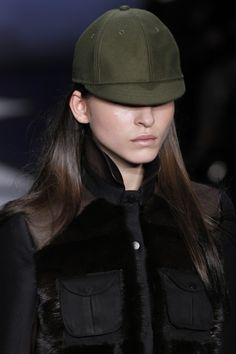 Perfect for a cool weather baseball game- an olive baseball cap and fur-trimmed jacket at Jen Kao. Photo: Fairchild Archive