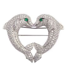 An iconic brooch from Cartier's limited Dolphin collection, presenting brilliant cut diamonds and emerald eyes on a platinum mounting. Circa 1990